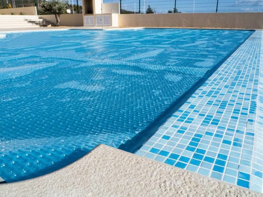 Here is a solar cover laying on the water. This cover helps heat the water using the sun's beams, keeping the water warm and ready to swim.