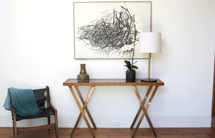 Simple console table and chair provide a welcoming and simple entryway.