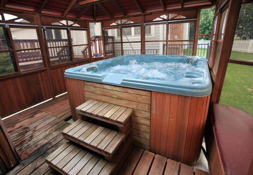 With a small patio, some simple walls, and a roof you can make your hot tub usable even in inclement weather. Soaking in hot water during the cool rain or even snow is a unique and relaxing experience.