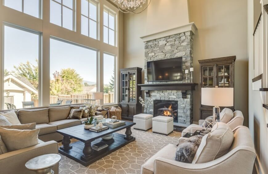 Two ottomans sit near a fire in this living room. These serve as great seats for sitting by the fire. They are small enough that they can also be moved and used as foot rests for any of the chairs in the room at a moments notice.