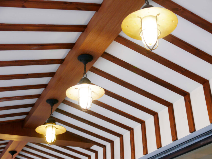 Here is a vaulted ceiling with a wooden design element that provides a extra visual appeal. The height of the ceiling lets the pendant lighting hang and not intrude into the space of the room.