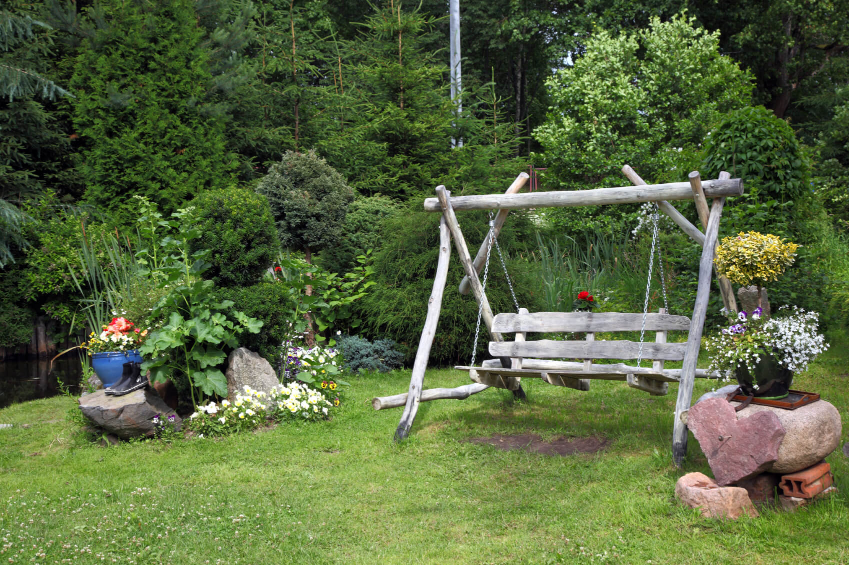 Here is a swing with a raw wood feel, which appears to be made from found and unfinished wood. This looks great out in a garden, amongst the large stones and near a stream. This natural wood design blends well into nature.