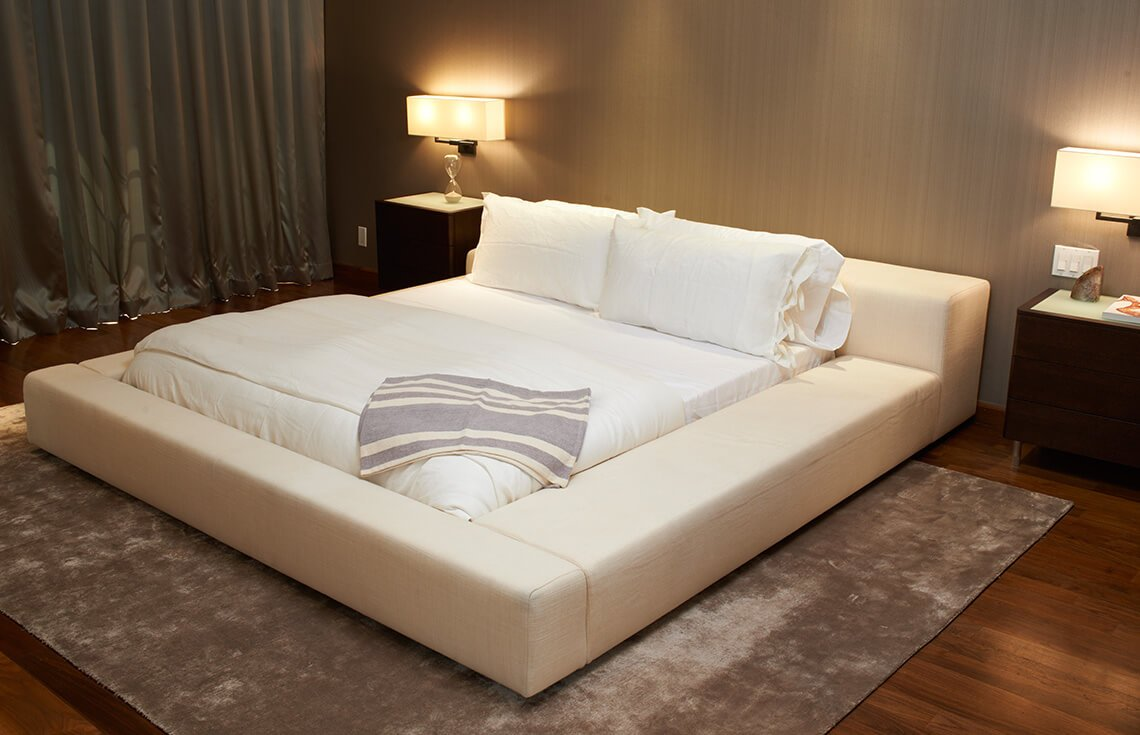 The sheer size of this bed frame makes the bed the focal point of the room, and the texture in the area rug furthers this effect. Plenty of lamps ensure that even during an evening showing, this room has plenty of light.