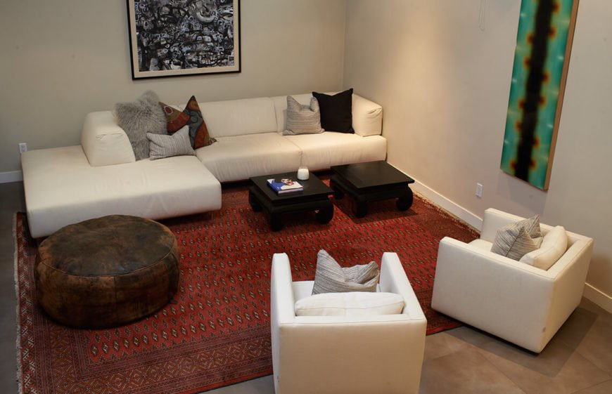 This living room does not have much access to a great deal of natural light, so the use of a bright colored sofa, chairs, and walls in tandem with artificial lights to bring a bit of brightness.