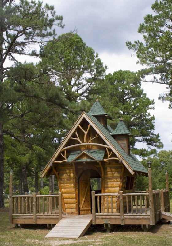 A raised wrap around deck and branched details make this playhouse feel like a treehouse, without the altitude.