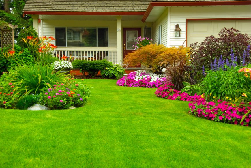 This well manicured lawn has several beds of flowers. The flowers in these beds have blooms of various sizes to create layers. With shorter flowers in the front, and long flowers at the center of the bed, it creates a fountain of color.