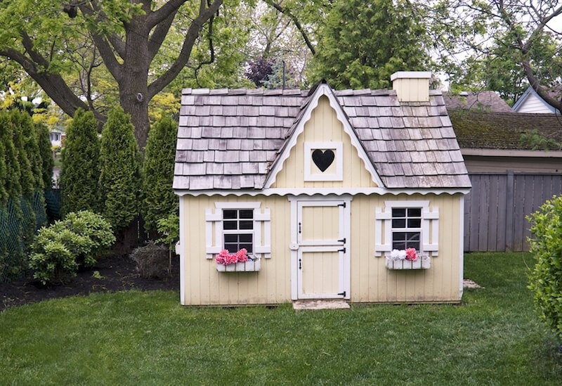 Childeren's playhouse with window shutters and window planter boxes.