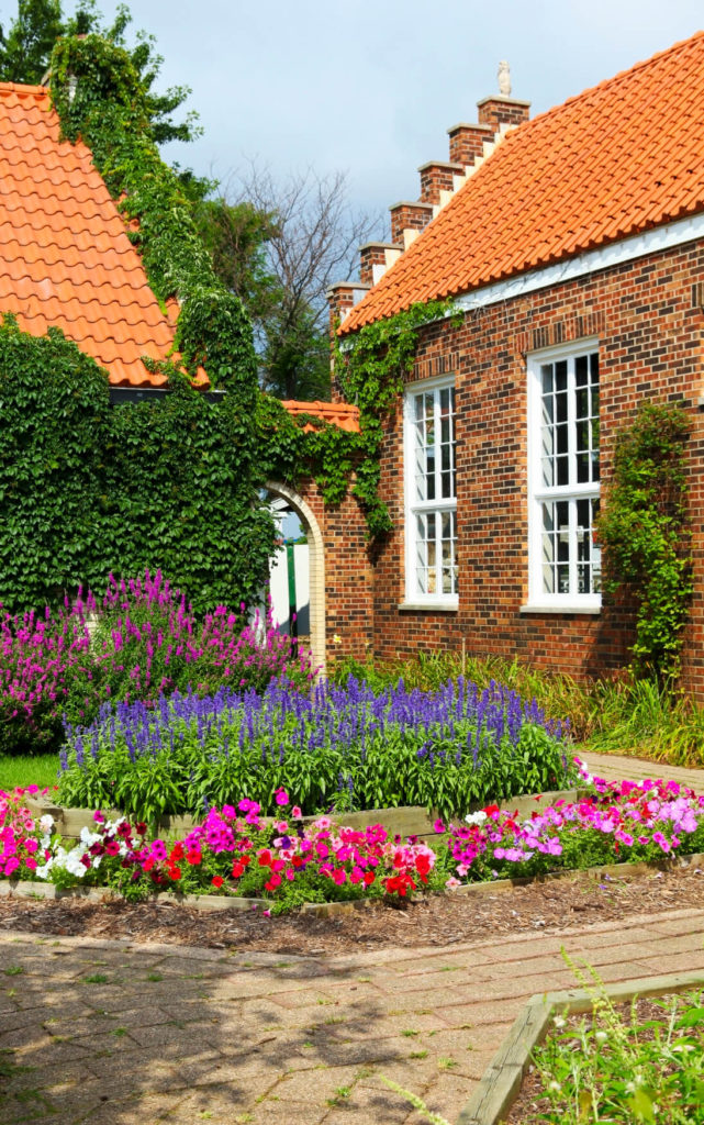 This lovely flowerbed has multiple levels, each level with its own set of colors. The warmer colors line the bottom of the bed as the cooler colors adorn the top. Separating the colors in a flower bed creates a sense of organization and order to your garden.