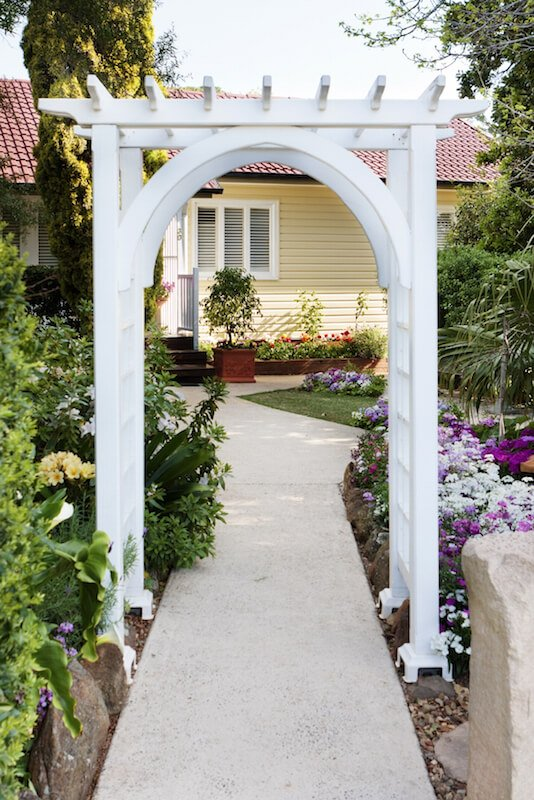 An entryway arbor that rests over the top of a concrete pathway leading through the front yard and up to the small porch.