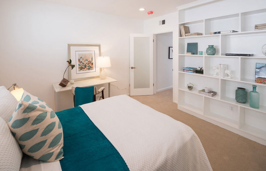 This bedroom is a great way to showcase the principle of arranging items on shelving. Not every shelf is full, but the items are varied in shape, color, and texture, creating that magazine-look that so many covet