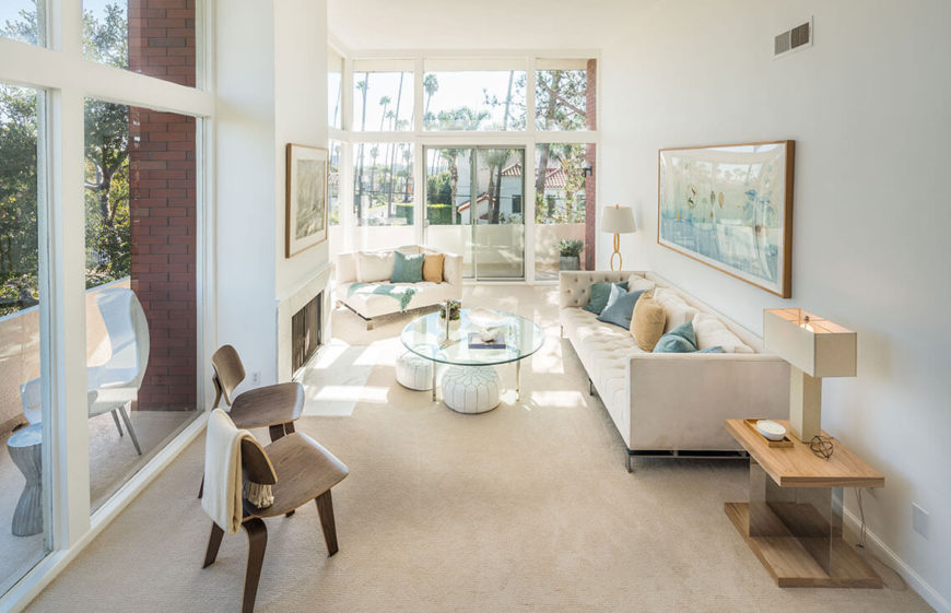 This living room has multiple large window areas to really let the sunlight shine in all times. The multiple pieces of artwork are well placed and give a sense of where this space can be personalized, but is still general enough that anyone walking through can imagine themselves living here.