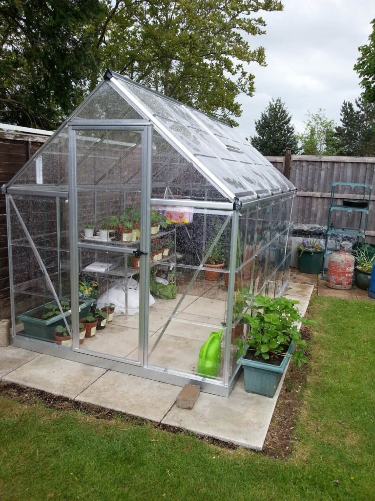 This is a small freestanding greenhouse on a stone stab out in the yard. This is a perfect small greenhouse for additional gardening, and extending the grow season of a few select plants.