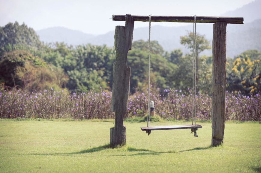 This swing is suspended from a simple archway with a flat plank seat. If you don't have many trees nearby, this is a workable alternative to hanging the flat plank seat from a branch.