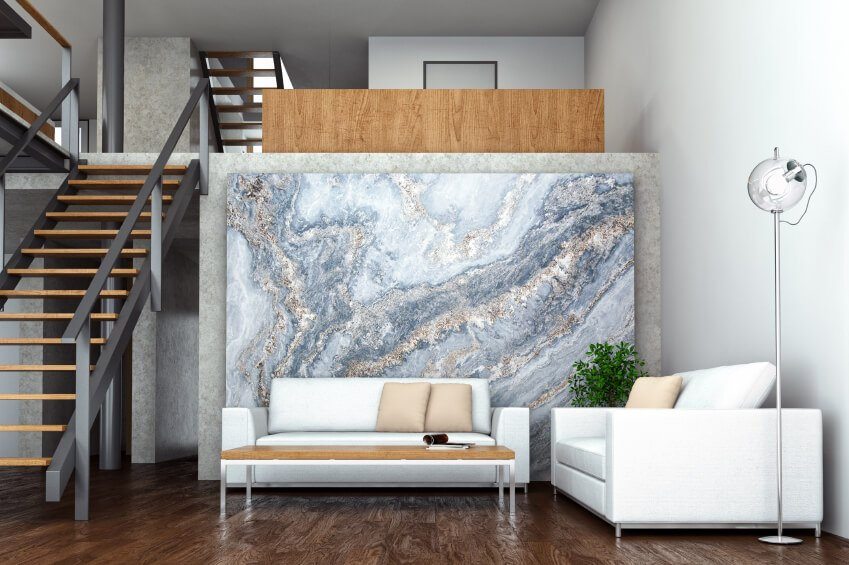 This living room has simple white walls which provide a great stage for design elements such as the slab of marble that sits behind the couch.