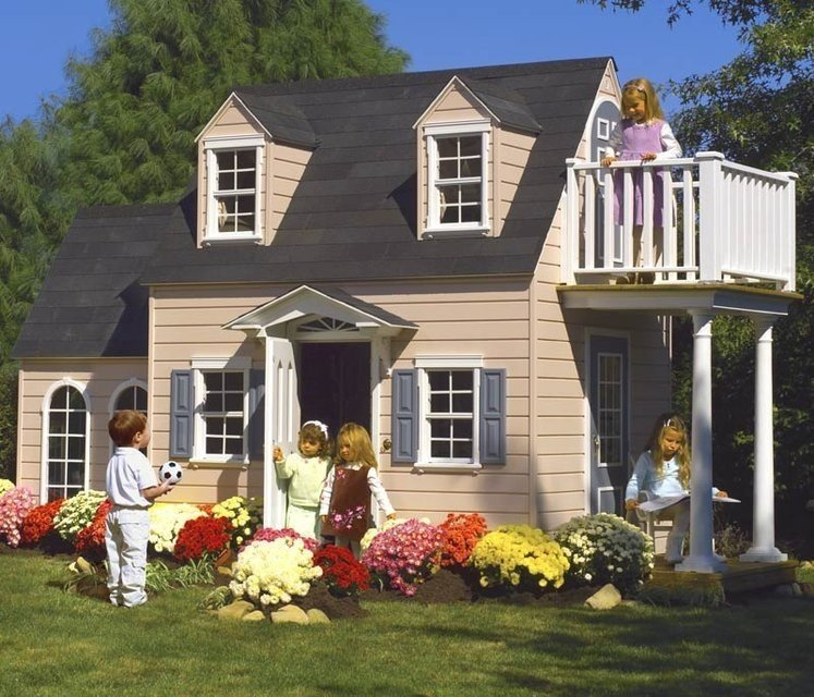 Colorful mums surround this incredible playhouse. Consider adding interesting details like painted shutters and a balcony to your child's playhouse.