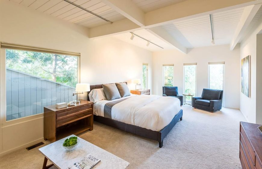 This bedroom is spacious and includes a wealth of windows, which are all unshaded, letting as much light in as possible. Bedside lamps are also included and turned on, for extra light. The walls are in a light, neutral color, with color pulling the eye to the bed.