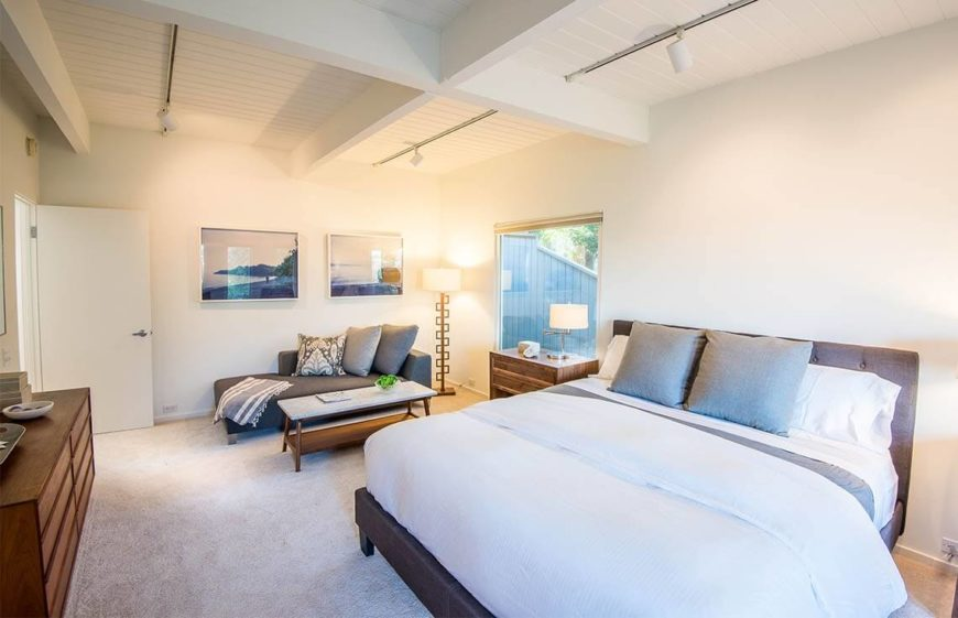 From the other side of the bed, we can see the small seating area in front of the largest window, furnished with a luxurious chaise lounge and punctuated by two landscape images above