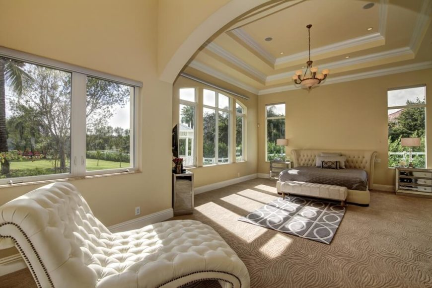This simple and bright living room has an interesting tray ceiling that has multiple levels. This creates even more space and depth to the room. The two toned layers of the tray ceiling also creates some contrast to the element, making it seem even deeper and more open.