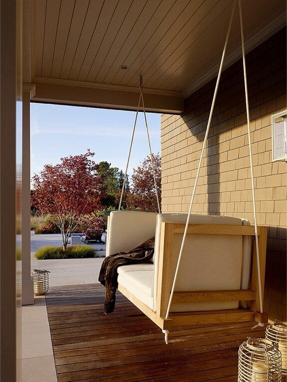 Here we can see a simple and modern porch swing with a bench seat. This is is an amazing place to sit in the evening, wrapped in a blanket reading a book or enjoying the sunset sipping your favorite beverage.