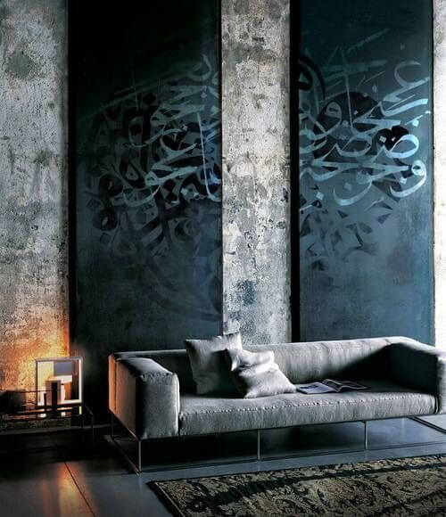 Here is a minimalist living room with concrete walls. These walls have a warn and interesting textures. The warn and distressed nature of this wall gives this room a lot of character.