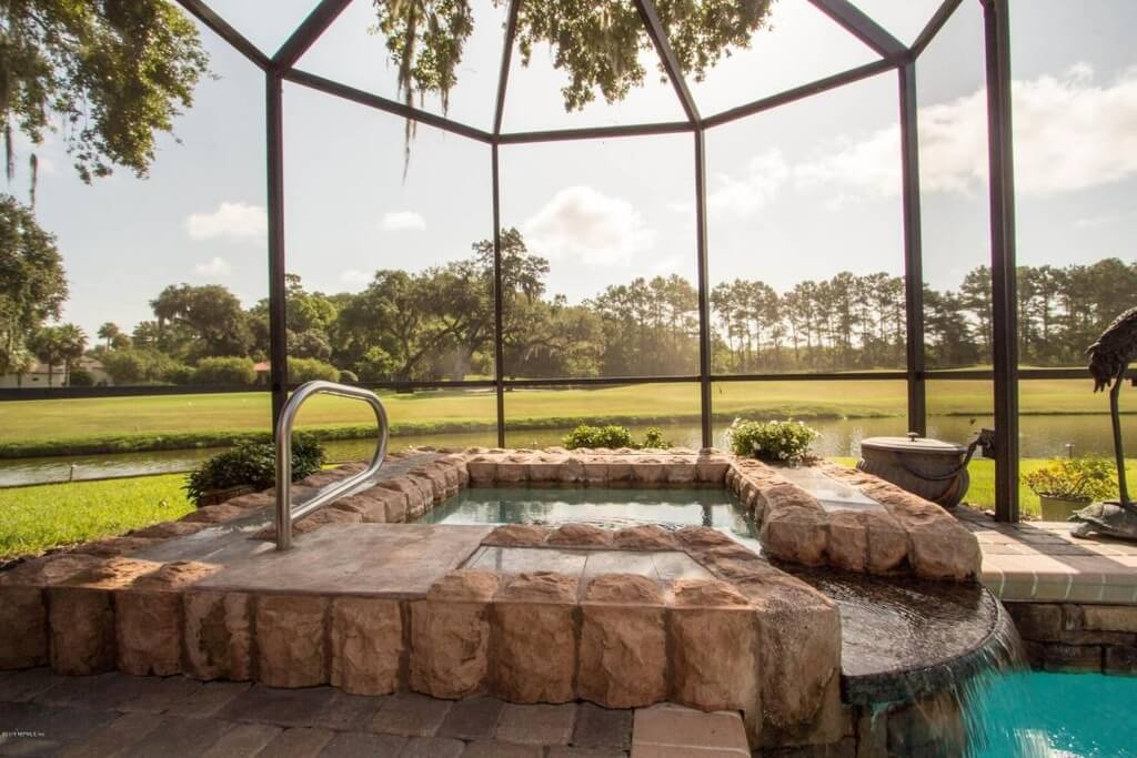 There are lots of ways to incorporate a hot tub into a pool area. A stone edge and a waterfall are great additions that both separates the hot tub into its own section and ties it into the rest of the pool area.