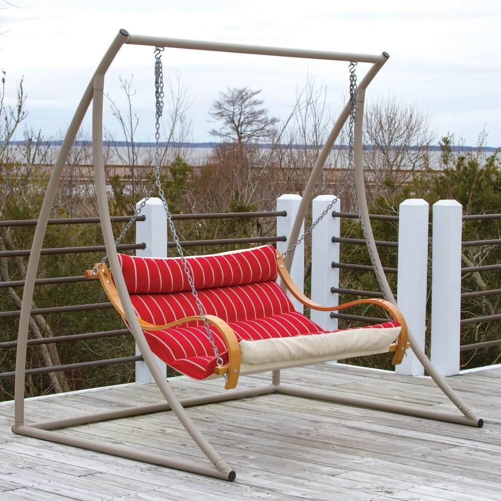 In this picture, there is a sleek and simple yard swing that has a leaned back and relaxed seat. A metal frame is a durable styled frame that has a small and simple profile. A metal frame does not need to be as thick as other materials to have equal or even greater weight bearing capabilities.