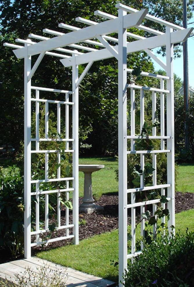 This is a more modern example of an arbor, with a non-traditional lattice pattern. Wooden steps lead up to the arbor before transitioning into soft, thick grass.