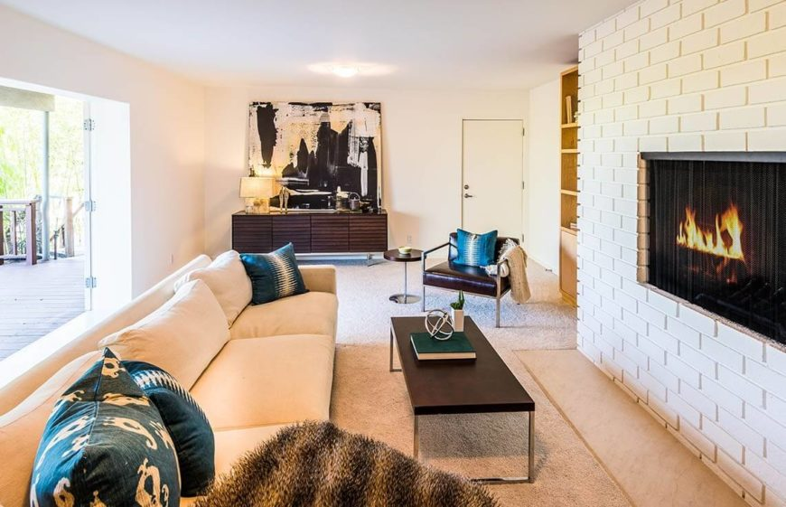 The natural light and light colors work well to really illuminate and brighten this living room. The stage items are placed in small groups to make the space feel inhabited but not cluttered.