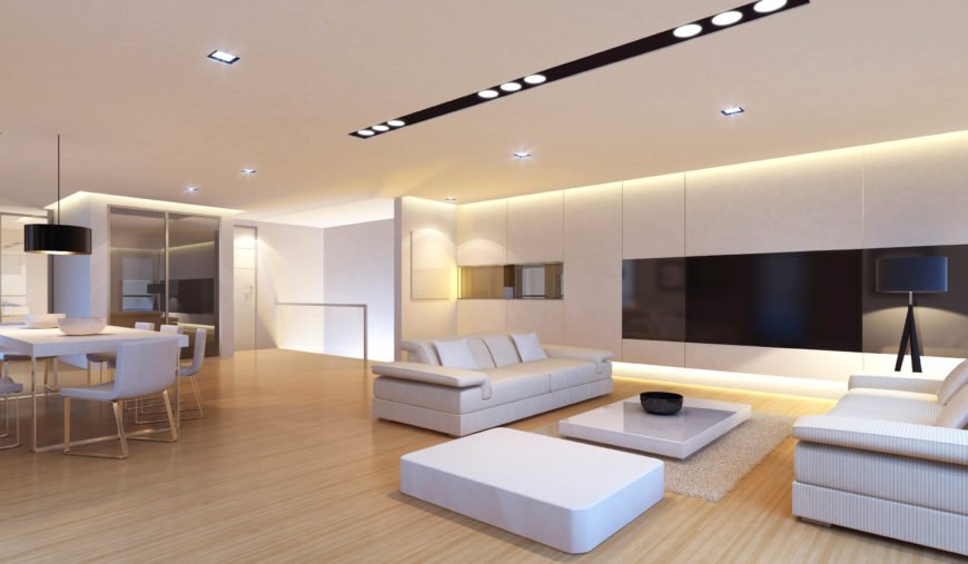 Here is a bright and simple modern living room that uses a number of simple recessed lights to brighten up the area. The black and white decor and natural wood floors reflect the light well, making the space really light up.