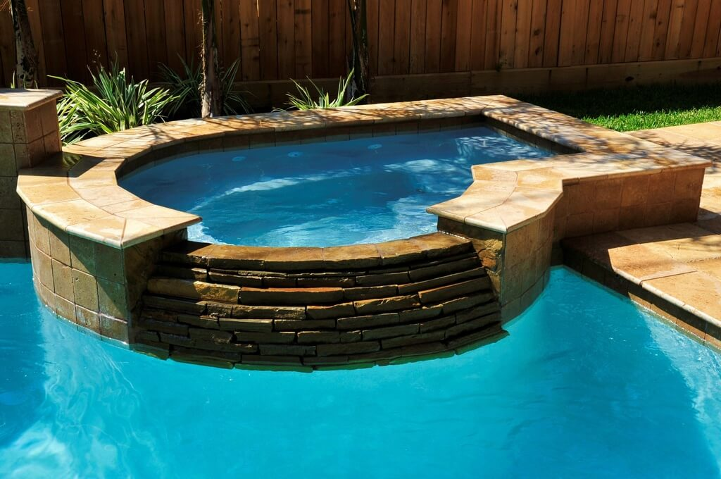 This is a picture of a nice personal hot tub next to a pool. It is so close you could step from one into the other.