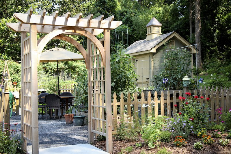This simple wooden arbor rests at the entrance to a backyard patio to one side of a shed. The patio is squared off by a simple picket fence.