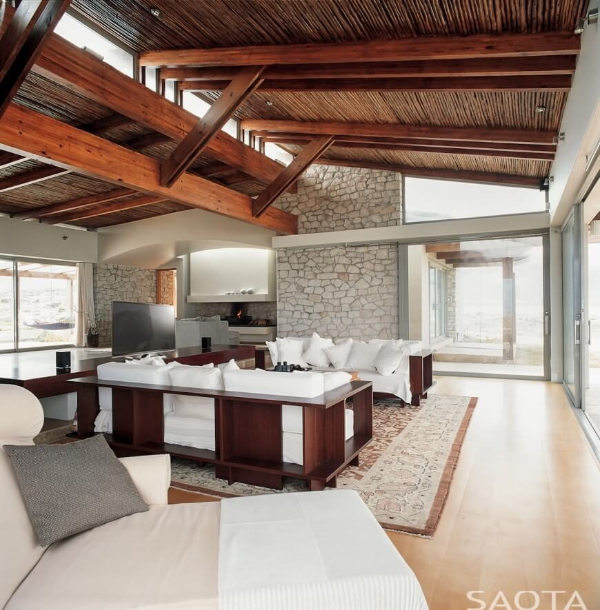In this modern and simple living room, the exposed beam ceilings, along with the masonry walls, gives a open and spacious appeal. The skylights incorporated into the ceiling help funnel the light in, brightening the room.