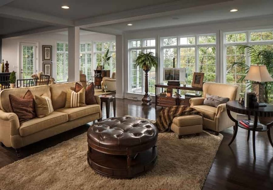 Swanky living room featuring dark wood floors and a leather ottoman.