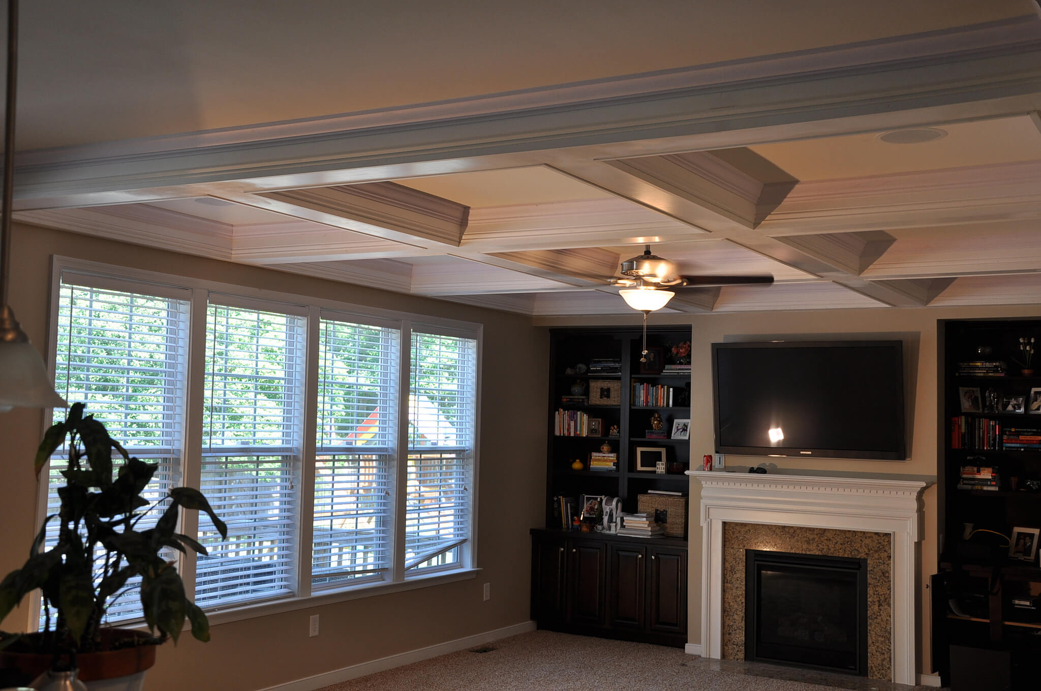 This living room has a white painted coffered ceiling. This coffered ceiling is a simple and elegant way to add some depth to your living room.