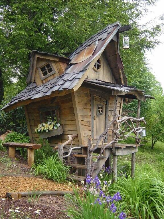 Off kilter door frames and rooflines make this playhouse funky and fun! An especially nice touch is the incorporation of branches for railing along the stairs.