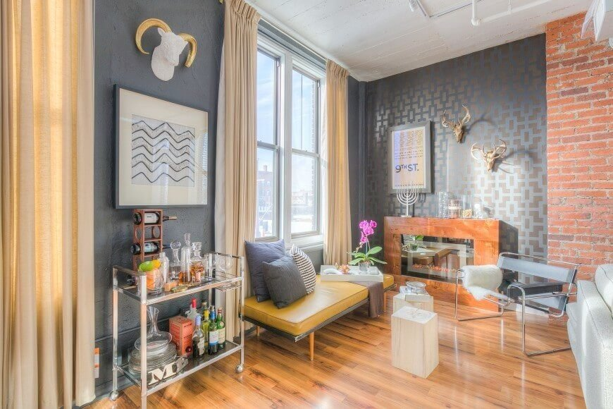 In this living room, there are multiple different kinds of walls working together. A simple blue wall, along with some exposed brick and a painted pattern all bring different elements to this room, creating interesting visuals.