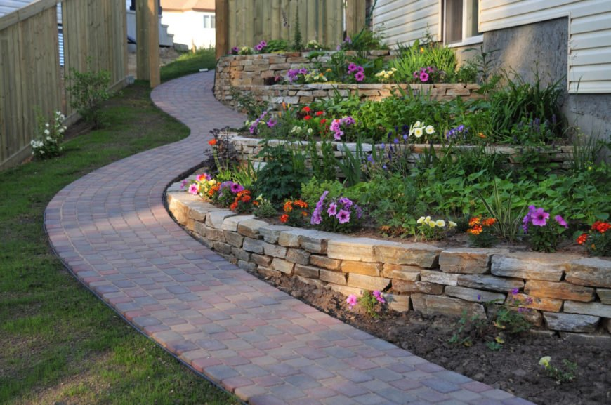A stone garden bed looks great when paired with a stone walkway. Stones are a great way to make a multiple leveled garden bed, as stone stacks well even on uneven ground.