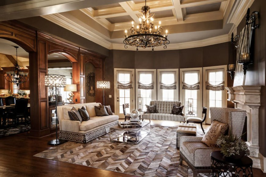 This picture shows a living room rich in nice wooden tones, and elegant furniture. To match this look, the light is provided by a stunning and intricate chandelier made from wrought iron.