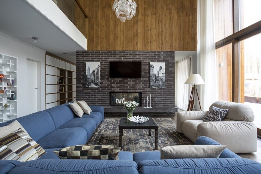 Around this fireplace , we can see some interesting dark colored bricks that work as a contrast to the brighter colors found in the rest of the room. Above the brick is a natural tone wood plank wall. These textures work well together as contrasting elements.