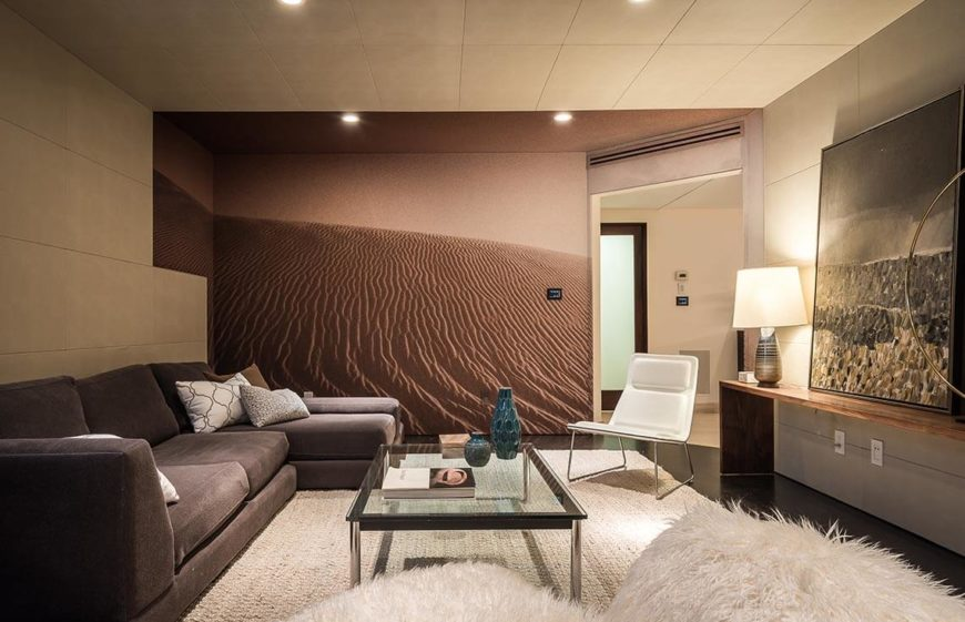 With a room where there are not many opportunities for natural light, using light colors and artificial lights to brighten the space is the best option. Here the white carpet, furnishings, and pillows bring some brightness to this space.