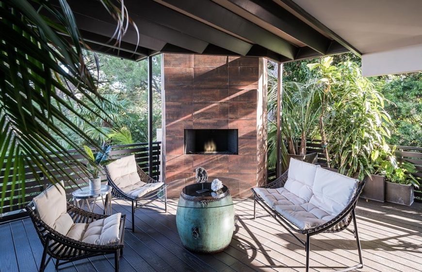Covered patio with a small fireplace and plenty of seating space.