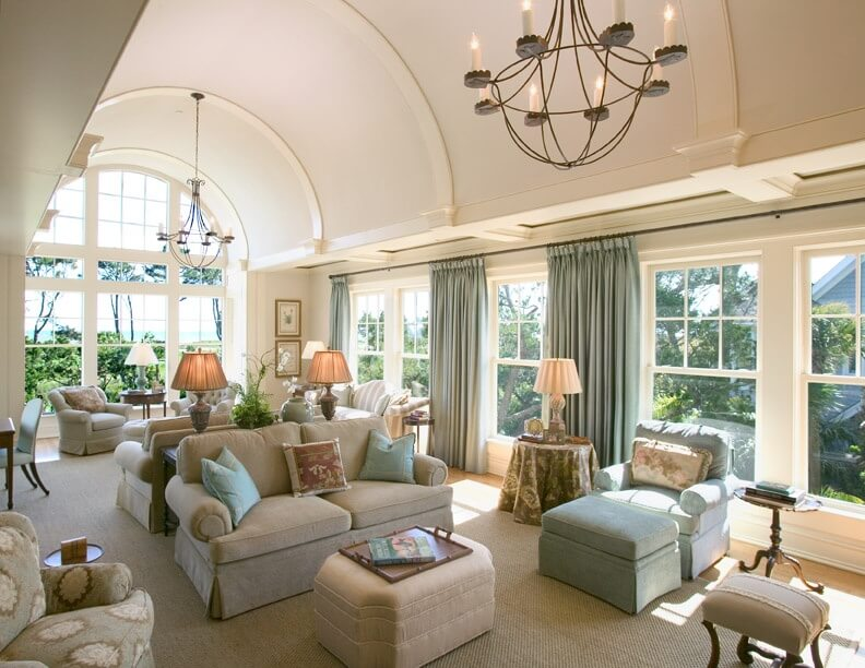 A large and luxurious living room is shown here under a bright and curved vaulted ceiling. The vault in this ceiling is almost like a long tunnel down the center of the room. Vaulted ceiling can come in many different arrangements, and can be formatted to fit different spaces and needs.