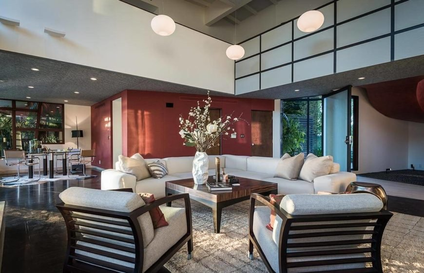 Here the sun soaked living room has light colored furnishings and white flowers to increase the brightness. The furniture is also away from the walls and placed in a balanced and symmetrical space to build a lovely conversation area. This uses the space well, and makes the room appealing.