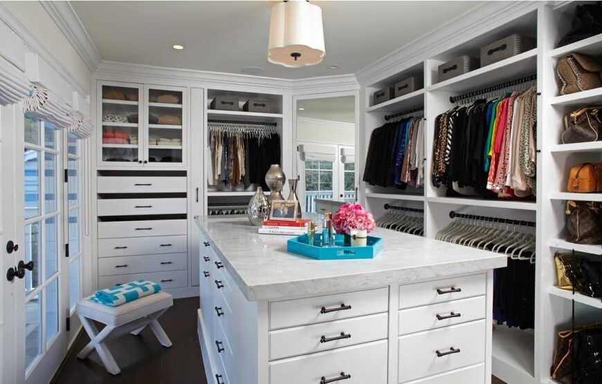 """This incredible walk-in closet still has lots of clothes in it, but all the hangers match, purses and shoes are in designated areas, and only a few neat accessories are sitting out on the """"island""""."""