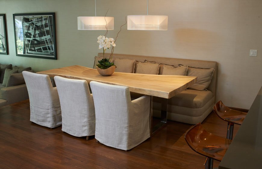 This is a simple and clever staged dining room. The seating consists of two different kinds of chair, around a unique wooden table. The simplicity of this design makes it an appealing area, and keeping the seating against the wall as it is, makes for good flow in an unconventional dining space.