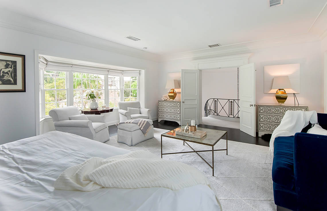 This spacious primary bedroom is in white and utilizes lamps and mirrors to help reflect light throughout the spacious room. A seating area is arranged in front of the large bay windows. A splash of color is brought in via the navy velvet sofa.