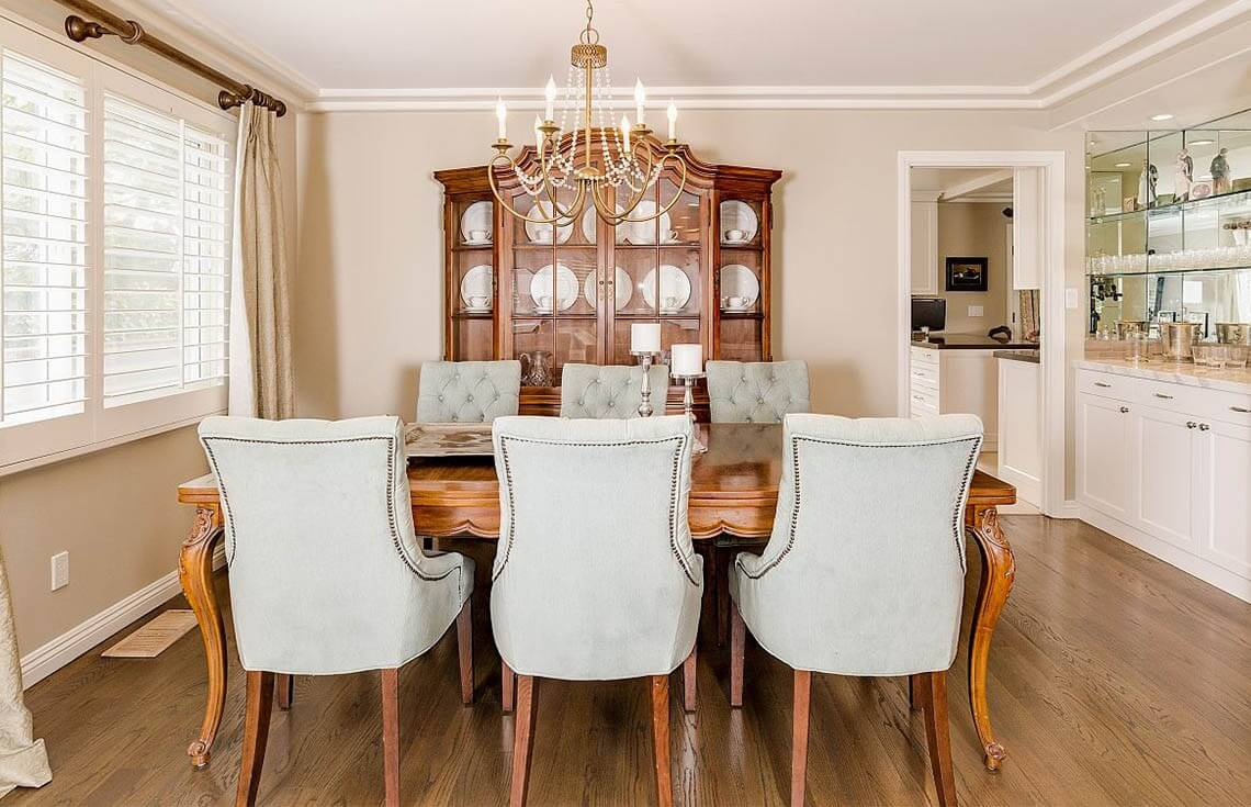 This is a good example of a bright and welcoming dining room with plenty of warm, natural light, and a easy flow and good use of space. The bright colors make this space attractive and inviting for prospective buyers who can picture themselves and their family around this elegant table.