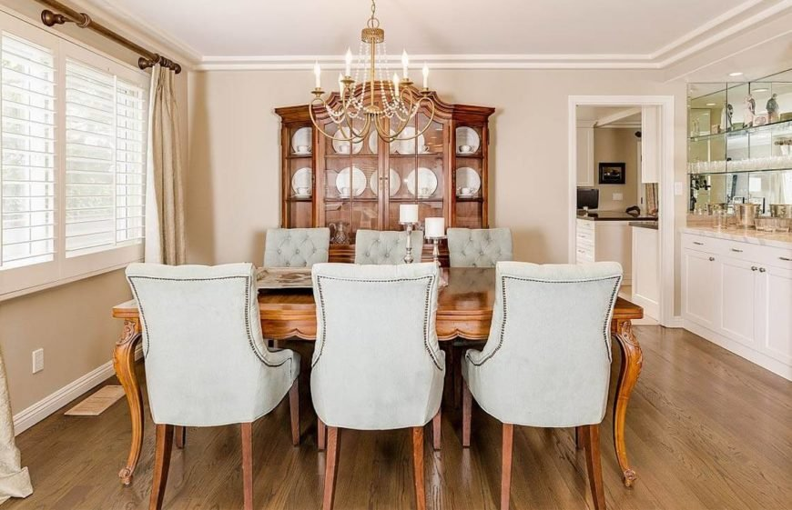 Elegant traditional dining room with neutral walls and rich wood details.