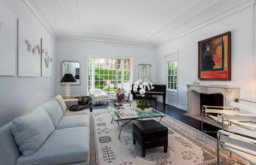 Another angle on the same room shows us the large and unobstructed windows letting the light in. There are also twin chairs near the windows, creating a bit of symmetry. Two mirrors hanging on either side of the windows also help create a deeper dimension and increase the perceived space a great deal