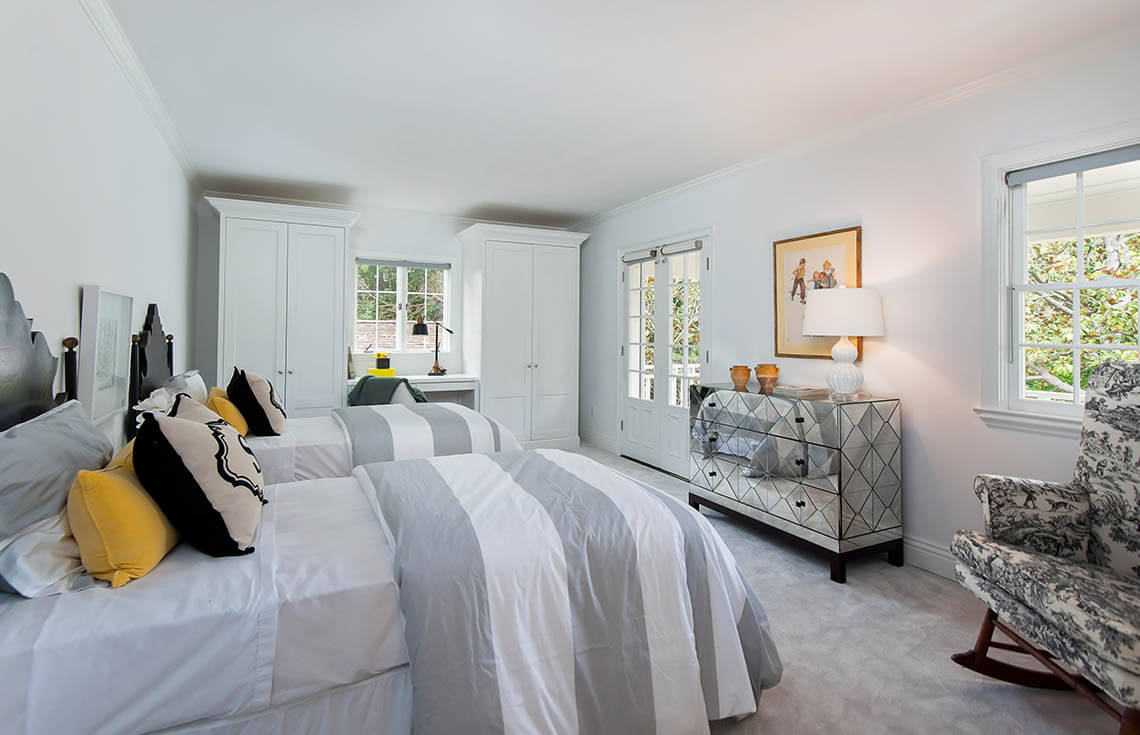Soft colors like gray and charcoal can be used safely in a mostly white bedroom to provide contrast and color. A simple vintage print was introduced to the design to tie into the yellow throw pillows.